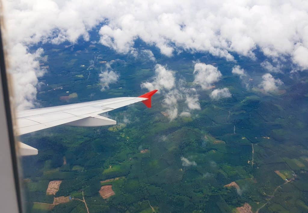 plane wing and lush green landscape form the air
