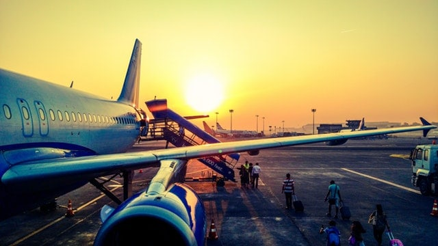 People boarding a plane at sunrise